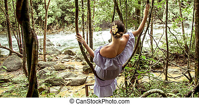 girl in a dress in the rain forest