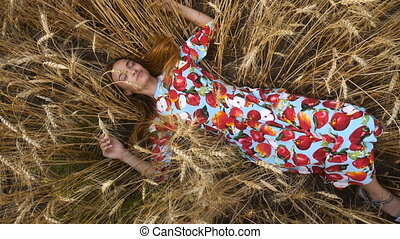 young girl in a dress lies in the wheat field and smiles