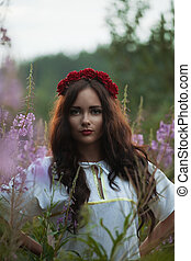 Beautiful young girl in a field on the background colors
