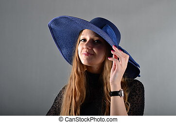 Beautiful young girl in a hat and a