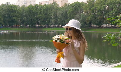 Beautiful young girl in a light dress and a white hat is walking in the park.