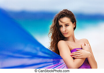 beautiful young girl in a purple cloth on a tropical beach
