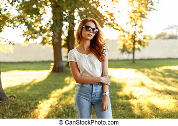 Beautiful young girl in a white T-shirt and vintage jeans with sunglasses in the park on a sunny day.