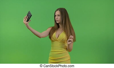 Beautiful young girl in a yellow dress, on a green screen. She takes pictures of herself on a smartphone.