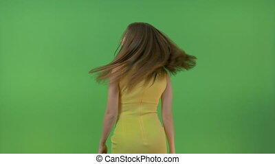 Beautiful young girl in a yellow dress, on a green screen. She turns and makes a gesture with her hand.