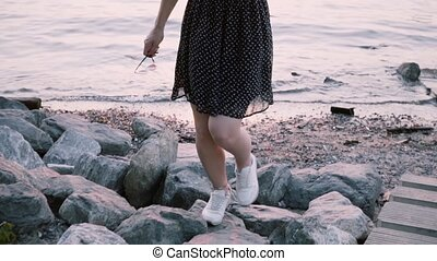 Beautiful young girl in black dress walking up on big river...