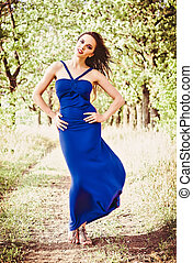 Beautiful young girl in blue dress among the trees