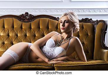 Beautiful young girl in bridal lingerie on a retro sofa