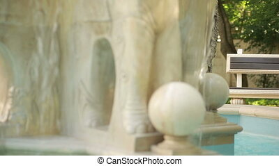 Beautiful young girl in dress standing near vintage stone fountain.