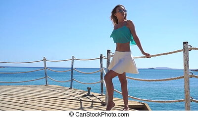 beautiful young girl in glasses standing on a pier near the sea and the wind is blowing in slow motion