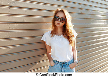 Beautiful young girl in high waist jeans near the vintage wooden wall.