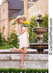 Beautiful young girl in light dress in the fabulous garden, holding bouquet of sunflowers