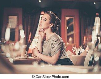 Beautiful young girl in luxury restaurant interior