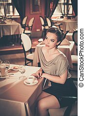 Beautiful young girl in luxury restaurant interior