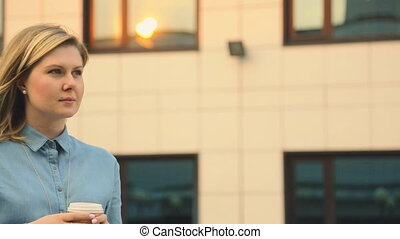 beautiful young girl in outdoor cafe drinking coffee. student. business woman