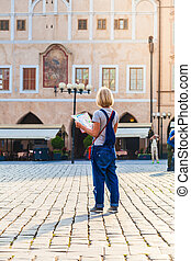 Beautiful young girl in Prague looks at the city map. -...