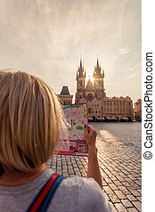Beautiful young girl in Prague looks at the city map.