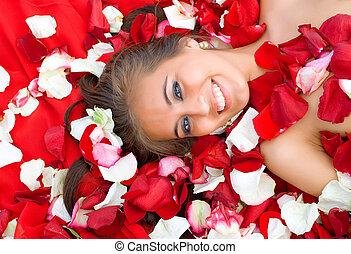 Beautiful young girl in rose petal