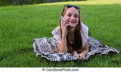Beautiful young girl in summer dress lies on grass in park, using smartphone. The girl has beautiful long hair. Happy beautiful smiling kid with glasses lies on green grass