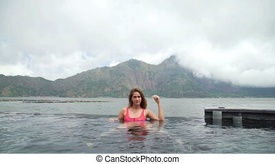 Beautiful young girl in swimming pool with lake and mountain...