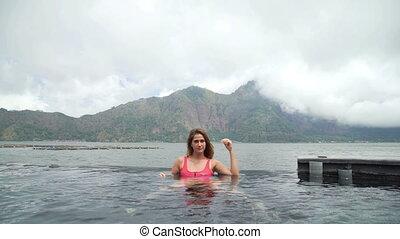 Beautiful young girl in swimming pool with lake and mountain...
