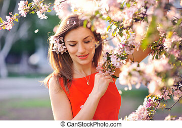 Beautiful young girl in the park and a flowering tree