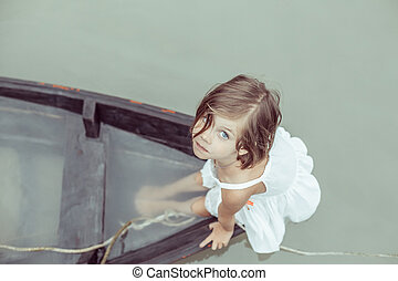 Beautiful young girl in the sinking boat.