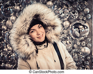 Beautiful young girl in warm fur clothes on the street standing near decorated wall with christmas balls. Fashion photo.