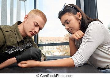 Blonde master in black gloves doing tattoo on female hand.