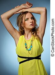 Beautiful young girl in yellow dress isolated on blue background