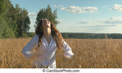 Beautiful young girl is happy on a wheat field.