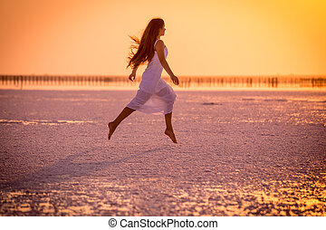 Beautiful young girl jumping on the salt lake at sunset
