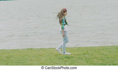 Beautiful young girl jumps on the coast lawn. Slow motion