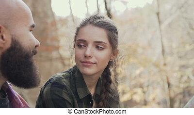 Beautiful young girl laughing happily, to a beautiful guy wearing a beard. Autumn Walking Youth