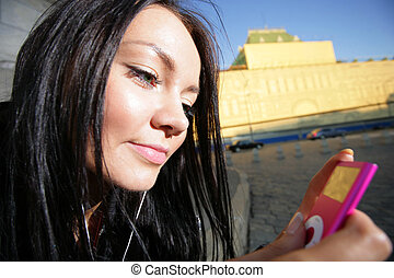 Beautiful young girl listening to portable music player,...