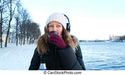 Beautiful young girl listens to music and drinks tea from a thermos in the open air in winter, warms in the park