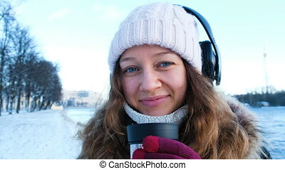 Beautiful young girl looking at the camera, listening to music and drinking tea from a thermos in the open air in winter, warmed in the park, portrait of a girl close-up