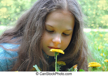 beautiful young girl Looking on dandelion flower