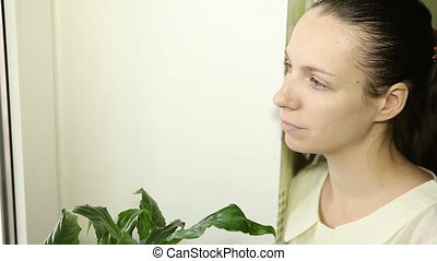 beautiful young girl looking out the window