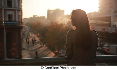 beautiful young girl  looks at the city