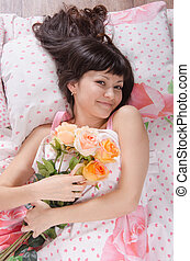 Beautiful young girl lying in bed with bouquet of roses