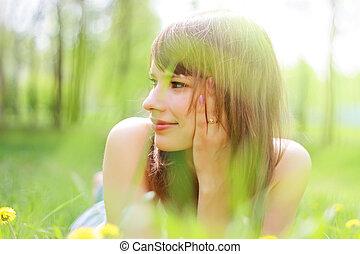 Beautiful young girl lying on grass