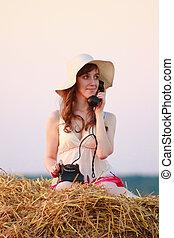 Beautiful young girl lying on haystack