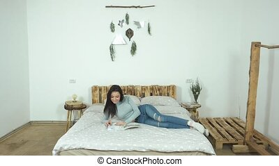 Beautiful young girl lying on the bed reading a glossy magazine