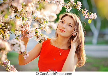 beautiful young girl on a background of flowering trees