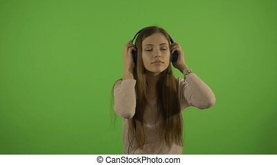 Beautiful young girl on a green background slowly dancing and listening to music through headphones.