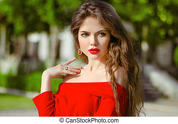 Beautiful young girl Outdoor portrait. Fashion brunette in red d