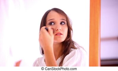 Beautiful young girl paints lips powder preens near the mirror. Video