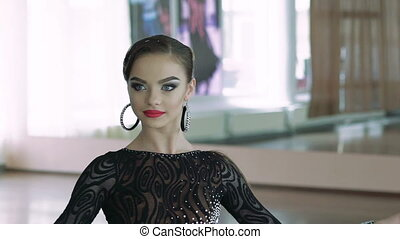 Beautiful young girl performs movements of ballroom dancing. Slowly