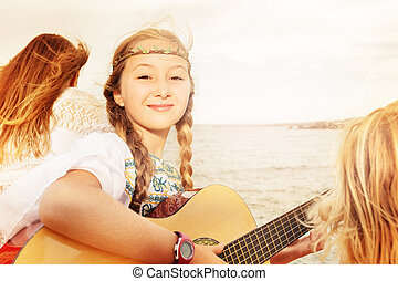 Beautiful young girl playing guitar on the beach